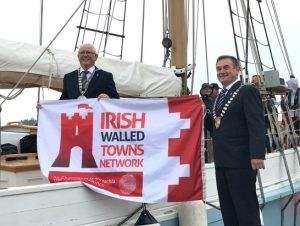 Two mayors wearing chains of office standing on the marina and on the sailing ship hold an Irish Walled Towns Network flag between them